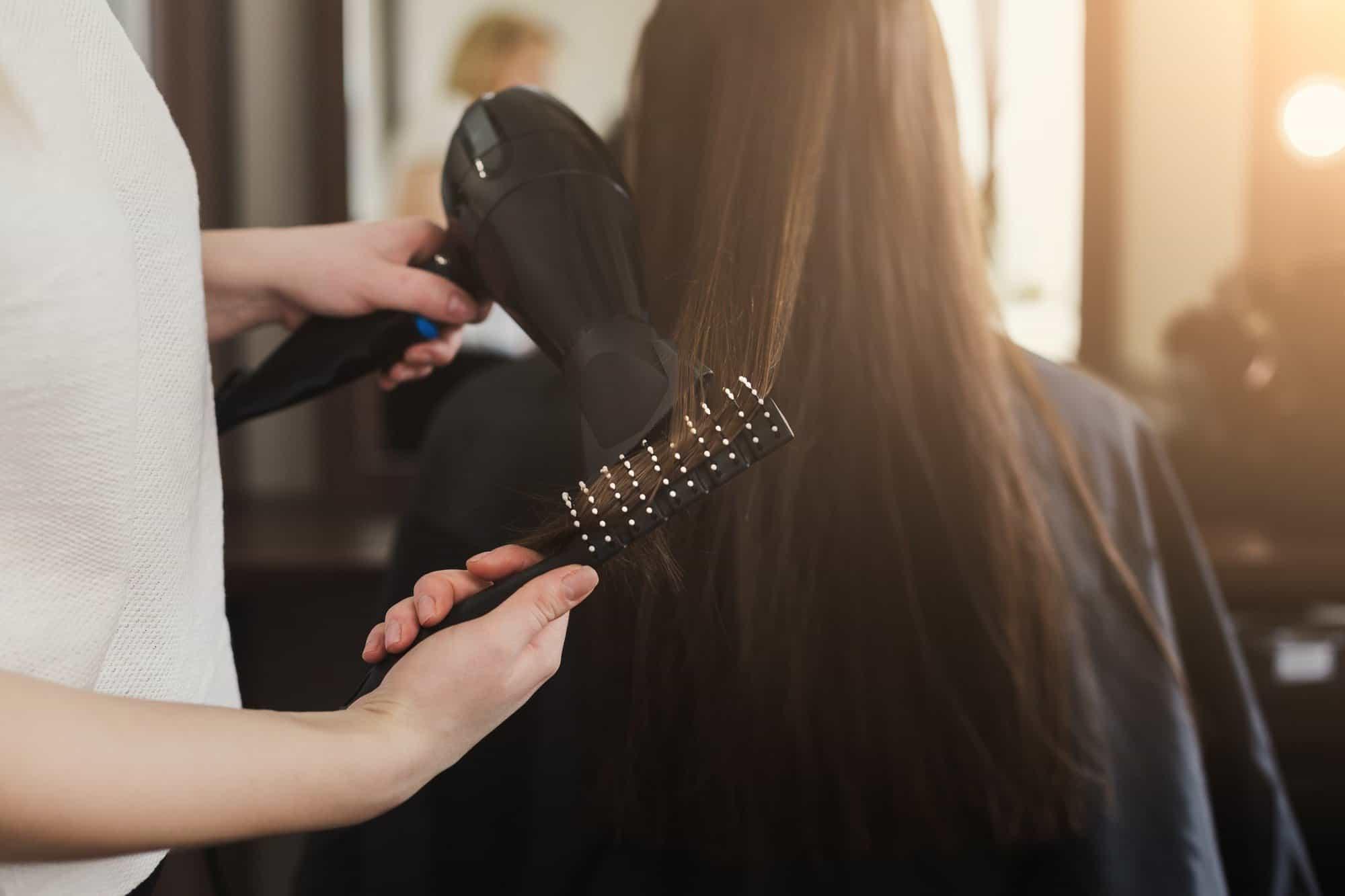 Beautician drying woman's hair